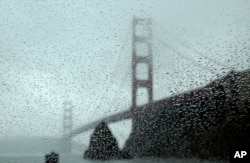 FILE - Rain drops bead on a car window below the Golden Gate Bridge, Jan. 5, 2016, in Sausalito, Calif. El Nino storms lined up in the Pacific, promising to drench parts of the West for more than two weeks.