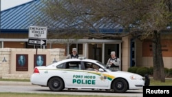 FILE - Military police guard the visitors center at the entrance to Fort Hood, Texas.