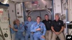 ناسا کی جاری کردہ اس تصویر میں امریکی خلاباز ڈگ ہرلی اور باب بینکن، بین الاقوامی خلائی سٹیشن میں پہلے سے موجود خلابازوں کے ساتھ کھڑے ہیں۔ 31 مئی 2020