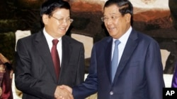 Cambodia's Prime Minister Hun Sen, right, shakes hands with his Laos Prime Minister Thongloun Sisoulith as they meet at Peace Palace, in Phnom Penh, Cambodia, Monday, June 27, 2016. Thongloun is on an official visit to Cambodia to further expand and strengthen the existing traditional relations of friendship, good neighborliness, and comprehensive cooperation between the two countries, according to a release. (AP Photo/Heng Sinith)