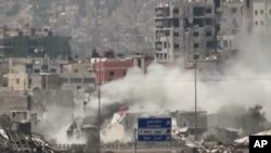 FILE - The Al-Qaboun neighborhood in rural Damascus is shelled, July 15, 2013.