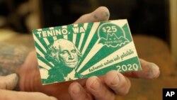 Loren Ackerman menunjukkan uang kayu yang dicetak menggunakan mesin cetak 1890an di Tenino, Washington, 21 Mei 2020. (Foto: AP)