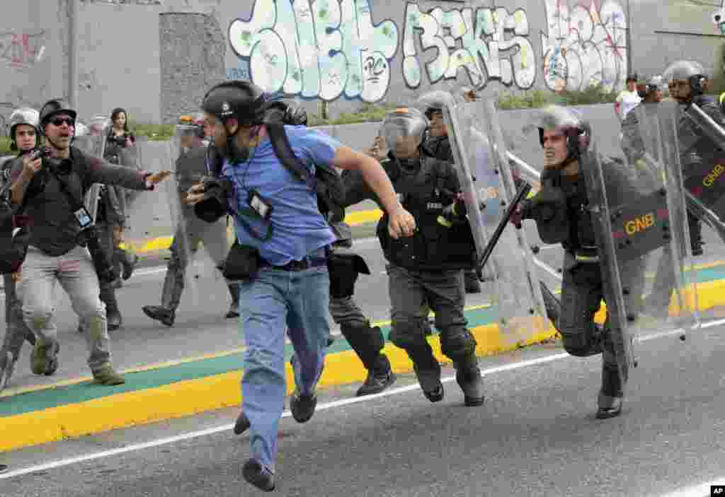 Reuters photojournalist Marco Bello runs as Venezuelan National Guard soldiers chase him during a protest outside the Supreme Court in Caracas. Security forces violently repressed small protests that broke out in the city after the government-stacked Supreme Court gutted congress of its last vestiges of power, drawing widespread condemnation from foreign governments.