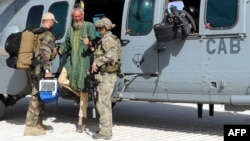 Dutch former hostage Sjaak Rijke (C) gestures next to two soldiers of the French special forces as he disembarks from a Caracal helicopter after being released, at a French Military airbase in Mali, April 6, 2015. (ECPAD handout photo)