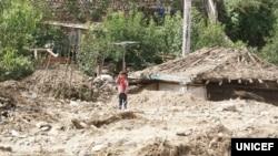 북한 함경북도 무산군 학산리에서 홍수와 산사태로 파괴된 마을에 한 아이가 서있다. 유니세프가 지난달 20일 발표한 북한 수해 실태 보도자료에 실린 사진.