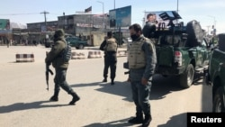 FILE - Policemen keep watch near the side of an attack in Kabul, Afghanistan, March 7, 2019.