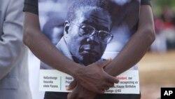Un partisan du président zimbabwéen Robert Mugabe tient le portrait de celui-ci lors des célébrations du 93e anniversaire de celui-ci à Matopos, dans la banlieue de Bulawayo, 25 février 2017.
