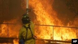 Seorang petugas pemadam kebakaran menyemprotkan air ke arah gedung Keysight Technologies yang dilalap api di Santa Rosa, California, 9 Oktober 2017.