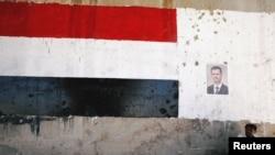 បុរសម្នាក់អង្គុយនៅក្បែររូបរបស់លោកប្រធានាធិបតីស៊ីរី Bashar al Assad ក្នុងពេលបើកផ្លូវចម្លោះពី ក្រុង Homs ទៅក្រុង Hama ឡើងវិញ នៅក្នុងប្រទេសស៊ីរី កាលពីថ្ងៃទី៦ ខែមិថុនា ឆ្នាំ២០១៨។