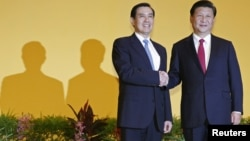 FILE - Chinese President Xi Jinping (r) shakes hands with Taiwan's President Ma Ying-jeou during a summit in Singapore, Nov. 7, 2015.