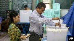 Một cặp vợ chồng bỏ lá phiếu của mình tại một địa điểm bỏ phiếu ở trung tâm thành phố Yangon, Myanmar, ngày 06/11/2015.