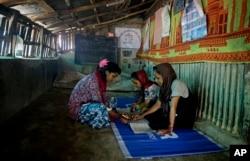 Rahima Akter, left, teaches her siblings inside the family hut in Kutupalong refugee camp.