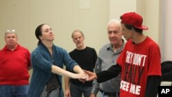 "Army veteran Carissa DiPietro takes the hand of Iraq war veteran Mike Mitchels while rehearsing for ""Julius Caesar"" in Milwaukee. A group of actors is using William Shakespeare's plays to help veterans with emotional and addiction issues heal, Sept. 27, 2015."