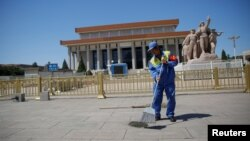 Уборщик перед Мавзолеем председателя Китая Мао Цзэдуна на площади Тяньаньмэнь по случаю 50-летия начала культурной революции в Пекине, Китай, 16 мая 2016.