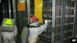 ພວກຄົນງານທີ່ໃສ່ເຄື່ອງປ້ອງກັນຢູ່ໂຮງໄຟຟ້ານິວເຄລຍ Fukushima ພວມປະຕິບັດໜ້າທີ່ຢູ່ຂ້າງໃນໂຮງໄຟຟ້າ (12 ພຶດສະພາ 2011)