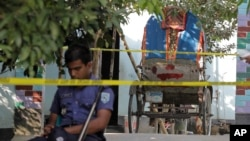 A Bangladeshi policeman sits next to a cycle rickshaw, on which Japanese citizen Kunio Hoshi was reported to be traveling while he was killed at Mahiganj village in Rangpur district, 300 kilometers (185 miles) north of Dhaka, Bangladesh, Oct. 4, 2015.