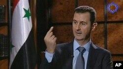 ຮູບພາບນີ້ຖ່າຍຈາກ ໂທລະພາບຊີເຣຍ ປະທານາທິບໍດີ Bashar al-Assad ກ່າວໃນລະຫວ່າງການສໍາພາດ ທີ່ກຸງ ເຕຫະຣານ ອີຣ່ານ ທີ 28 ມິຖຸນາ, 2012.