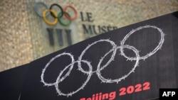 西藏新疆活動人士在洛桑用顯示鐵絲網編織奧運圓環的牌子抗議中國2022年主辦北京冬奧會。 (2021年6月23日)