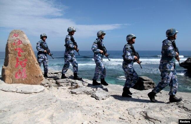"""中國海軍軍人2016年1月29日在帕拉塞爾群島(中方稱西沙群島)的伍迪島(中方稱永興島)巡邏。 岩石上的文字是""""西沙老龍頭"""",這是該島附近一堆岩石的名稱。"""