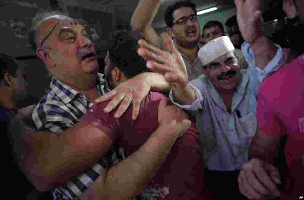 Palestinians mourn their relative in the morgue of the Shifa hospital in Gaza City on July 12, 2014.