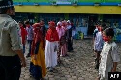 Siswa SD memakai masker, mendengarkan keterangan dari anggota tim siaga darurat (Tagana) saat program mitigasi penanggulangan virus Covid-19 di Banda Aceh, 19 November 2020.