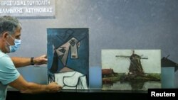 """The paintings """"Woman's Head"""" by Pablo Picasso and """"Mill"""" by Piet Mondrian, both stolen from Greece's National Gallery in 2012, are displayed during a presentation to members of the media at the Ministry of Citizen Protection in Athens, Greece, June 29, 20"""