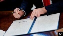 El presidente Donald Trump firma una orden ejecutiva en la Oficina Oval de la Casa Blanca en Washington el viernes 24 de febrero de 2017.