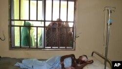 Des femmes tentent d'apercevoir une victime d'un attentat-sucide dans un hôpital de Maiduguri, au Nigeria vendredi 16 octobre 2015; (AP Photo)