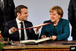 German chancellor Angela Merkel and French President Emmanuel Macron exchange documents during the signing of the new Germany-France friendship treaty at the historic Town Hall in Aachen, Germany, Jan. 22, 2019.