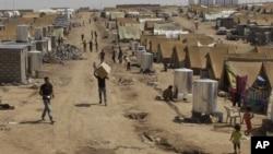 Syrian refugees walk through the Dumez refugee camp in Dahuk, northwest of Baghdad, Iraq, August 13, 2012.