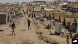 Syrian refugees walk through the Dumez refugee camp in Dahuk, northwest of Baghdad, Iraq, August 13, 2012.