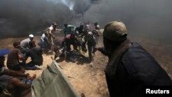 Warga Palestina mengevakuasi para demonstran yang terluka dalam aksi protes di Jalur Gaza, Senin (14/5).