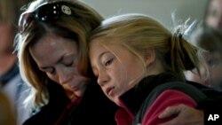 Madre e hija asisten a un servicio religioso en Newtown en memoria de las víctimas de la matanza.