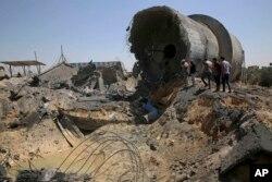 Trabajadores palestinos inspeccionan el daño en un centro municipal de distribución de agua después de un ataque aéreo israelí, en Mughraqa, en el centro de la Franja de Gaza, el jueves 9 de agosto de 2018.