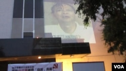 中領館牆上放映李旺陽香港媒體訪問錄象