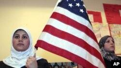 Seorang perempuan Muslim memegang bendera AS dalam sebuah acara di Islamic Center di Dearborn, Michigan. (Foto: Dok)