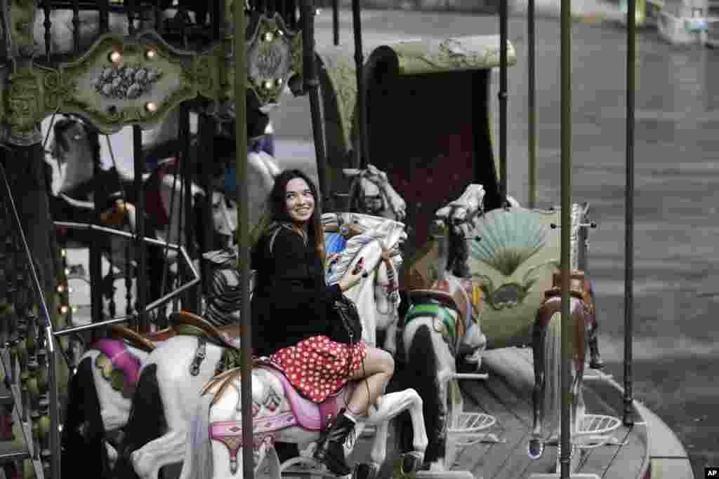 زن جوانی در «مونمارتر»، تپهای در شمال پاریس،کاروسل سوار شده است. اسباب بازی مخصوص کودکان که صندلی هایی به شکل حیوانات دارد و افقی و مدور می چرخد.