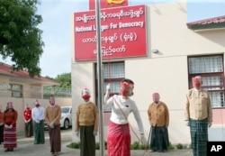 Pemimpin Myanmar Aung San Suu Kyi mengibarkan bendera partainya, Liga Nasional untuk Demokrasi pada hari pertama kampanye pemilu di Naypyitaw, Myanmar (8/9).