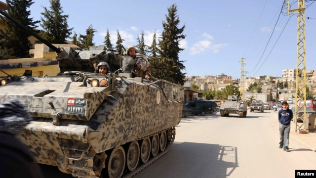FILE - Lebanese army soldiers patrol the Sunni Muslim border town of Arsal in an armored vehicle.