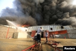 FILE - A crew battles a fire engulfing a warehouse of the World Food Program in Hodeida, Yemen, March 31, 2018.