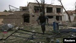 Seorang polisi Afghanistan tampak di lokasi ledakan yang dilakukan oleh militan Taliban di komplek PBB di Kabul (24/5).