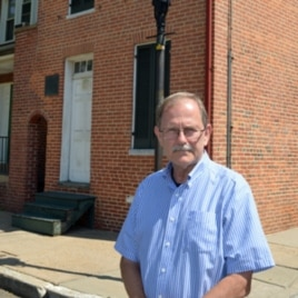 Curator Jeff Jerome stands outside of the house where Edgar Allan Poe lived while he was in Baltimore.