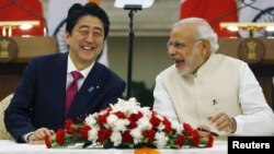 Japan's Prime Minister Shinzo Abe, left, and his Indian counterpart, Narendra Modi, share a moment during a signing of agreement at Hyderabad House in New Delhi, India, Dec. 12, 2015.