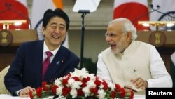 Japan's Prime Minister Shinzo Abe, left, and his Indian counterpart, Narendra Modi, shares a moment during a signing of agreement at Hyderabad House in New Delhi, India, Dec/ 12, 2015.