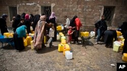 FILE - Women and children wait to fill buckets with water from a public tap amid an acute shortage of water, in Sana'a, Yemen, May 9, 2015. (AP Photo/Hani Mohammed)