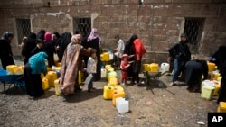FILE - Women and children wait to fill buckets with water from a public tap amid an acute shortage of water, in Sana'a, Yemen, May 9, 2015.
