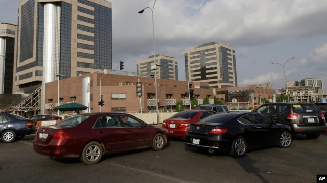 FILE- Cars line up in front of the Nigerian National Petroleum Corporation headquarters to buy fuel in Abuja, May 26, 2015. The global drop in the price of crude has battered Nigeria's economy, slowing economic growth and cutting into government revenue, March 1, 2016.