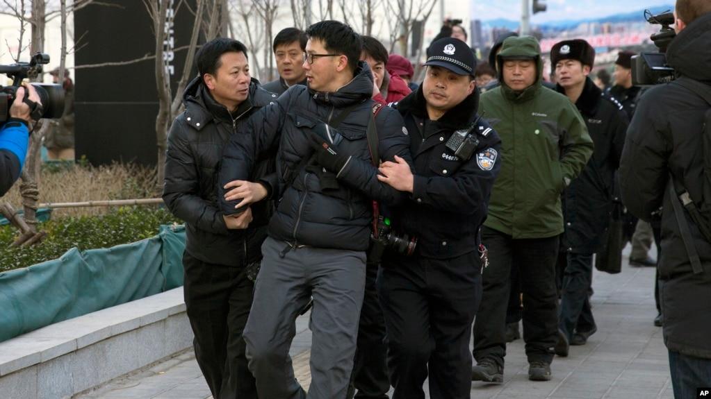 """资料照:在北京法院外面拍摄""""新公民运动""""发起人许志永等人的外国摄影记者被警察架走(2014年1月26日)"""