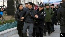 """在北京法院外面拍摄""""新公民运动""""发起人许志永等人的外国摄影记者被警察架走(2014年1月26日)"""