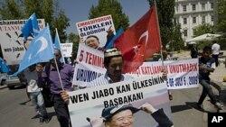 ជនជាតិភាគតិចវីហ្គ័រក្នុងប្រទេសតួគីកាន់រូបថតនាយករដ្ឋមន្រ្តី Wen Jiabao ជាការប្រឆាំងតវ៉ាដល់ដំណើរបំពេញទស្សនៈកិច្ចនាយករដ្ឋមន្រ្តីចិននៅប្រទេសតួគី ថ្ងៃទី៥ ខែមិថុនា ឆ្នាំ២០១១។